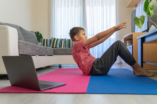 Teenager boy with laptop computer doing sport exercises, practicing yoga in the living room. Sport, healhty lifestyle, active leisure at home