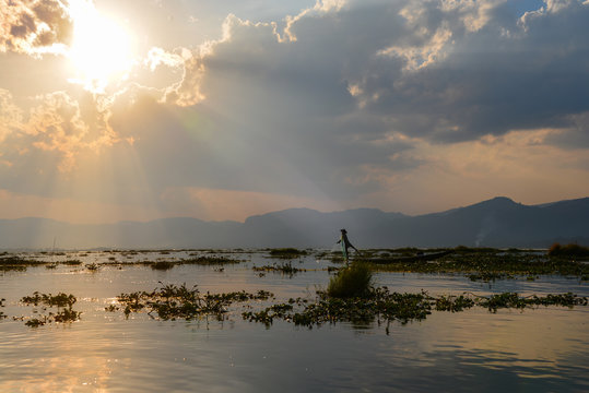Lake Inle fishermen gathers his net while he paddles the boat with his leg
