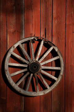 vintage wooden wagon wheel on red wooden rustic wall
