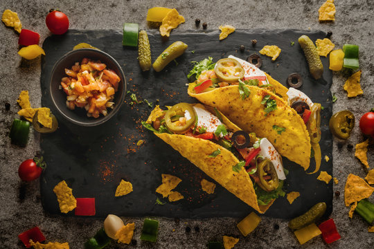 mexican food background of tacos on black slate plate in dark tone, selective focused