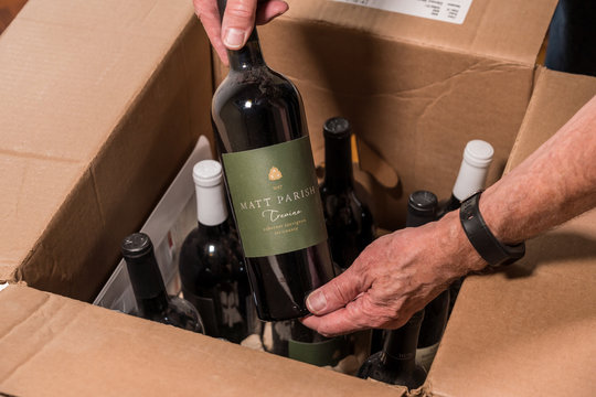 Senior man examining a case of wine from Naked Wines after home delivery