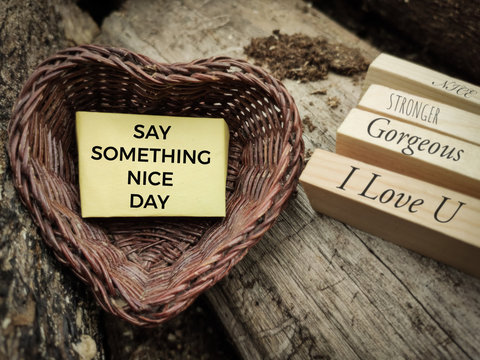 motivational and inspirational celebration concept - SAY SOMETHING NICE DAY text on notepaper inside heart shaped basket in vintage background