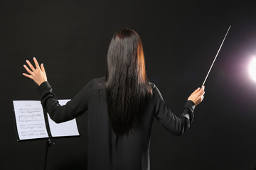 Young female conductor on dark background