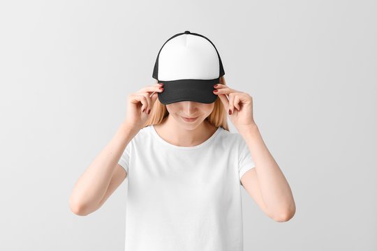 Beautiful young woman in stylish cap on light background