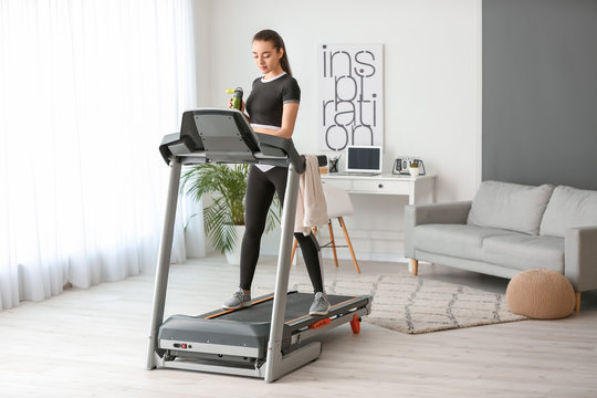 Sporty young woman training on treadmill at home