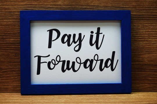 Pay It Forward written with blue photo frame on wooden background