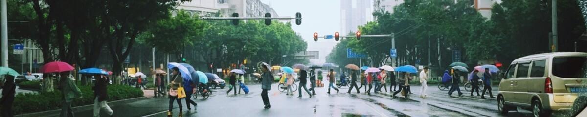 Panoramic Shot Of People On City Street During Rainy Season Fotobehang