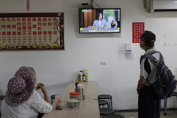 People watch the live inauguration ceremony of Taiwan President Tsai Ing-wen at a restaurant in a restaurant in Taipei,