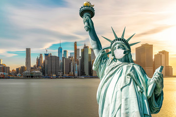 The Statue of Liberty wearing surgical mask when Covid-19 Outbreak over the Scene of New york cityscape river side, united state, coronavirus pandemic, Architecture and building with tourist concept