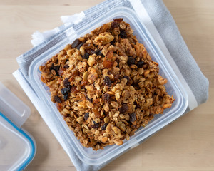 Healthy granola cereal with oats, pumpkin seeds, walnuts, and raisins in a plastic container