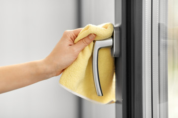 hygiene, household and cleanliness concept - close up of female hand cleaning window handle with...
