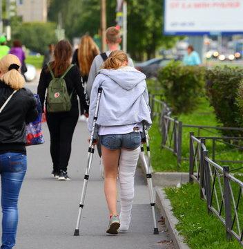 Girl on crutches Prospekt Bolshevikov Saint-Petersburg Russia September 2017