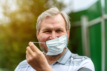 The man joyfully removes the medical mask from his face. End of the viral pandemic quarantine.