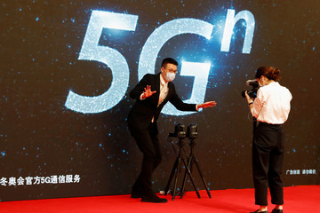 Reporter explains for the camera the technology involved in broadcasting the news conference by Guo Weimin in Beijing
