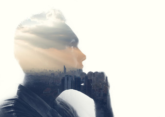 Double exposure portrait of a man in contemplation at sunset time above the city