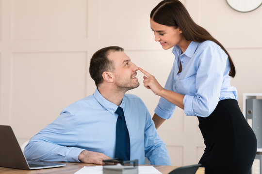 Businesswoman Seducing Male Employee Flirting At Workplace In Modern Office