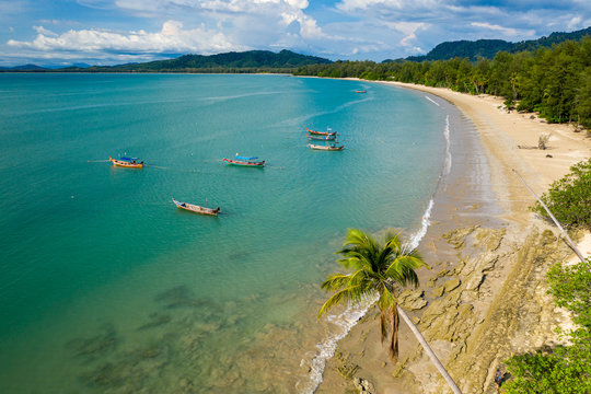Aerial view of a beautiful, empty tropical beach surrounded by palm trees with small wooden fishing boats