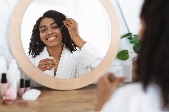 Skin nutrition. Beautiful black woman applying moisturizing serum on face at home