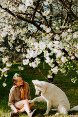 A woman with a white swiss shepherd under a cherry tree; friendship concept