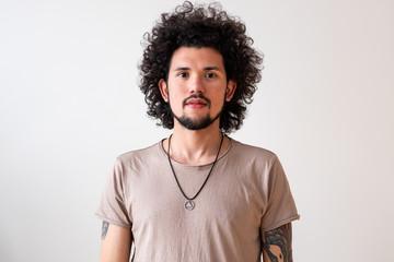 Latin American model slightly smiling, headshot, neutral background