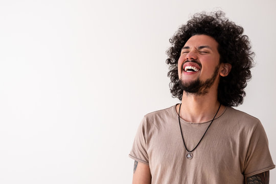 Latin American model laughing, wide smile, neutral background