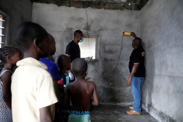 Children watch employees of Salpha Energy installing a music player powered by solar energy in their home at Sagbo-Kodji community in Lagos