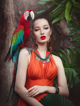 Portrait of young attractive woman in african style with ara parrot on her hand on a tropical background. Beautiful brunette girl in drungles with a macaw parrot.