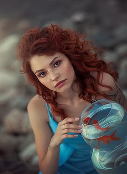 Portrait of a red-haired girl on the lake and an aquarium with a gold fish. Romantic image of a dreamy girl making a wish.
