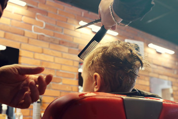 Professional hairdresser, fashionable men's hairstyle. A child, a boy, during a haircut at a barbershop.