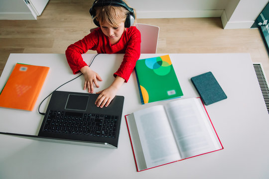 little girl on remote learning at home, kid making homework