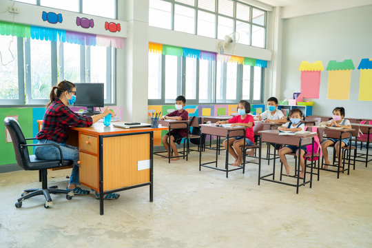 Group of school kids wearing protective mask to Protect Against Covid-19 with teacher sitting in classroom,education,elementary school,Social Distancing,learning and people concept.