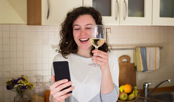 Happy young smiling caucasian woman making video call with smartphone at kitchen. Best friends drinking white wine and toasting. Video conference party online meeting with family. Stay home.