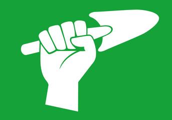 Concept de la plantation et du jardinage avec une main levée qui brandit un plantoir comme symbole de la reforestation.