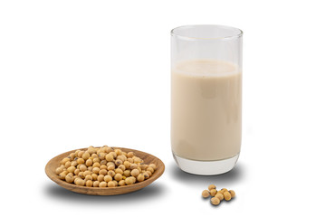 Fototapete - Soymilk in a glass and soy beans in a wooden plate on white background with clipping path.