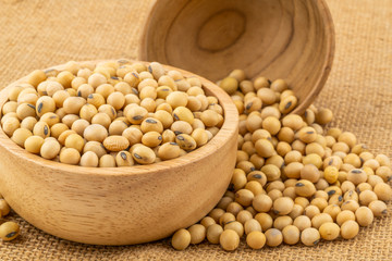 Fototapete - Soy beans in a wooden bowl with a  pile of soy beans on sackcloth