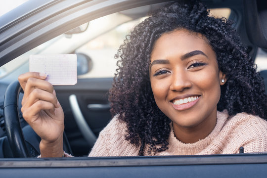 Young black woman at the wheel showing driving license
