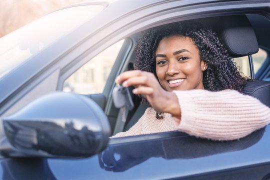 Young black woman at the wheel on her new car
