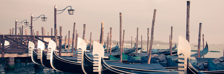 Wall Mural - Panoramic view of gondolas and wooden pier in winter in Venice, Italy