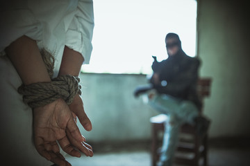 Back view of hostage woman with tie rope in hands,The thief pointed his gun towards him.