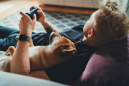 Young hipster guy playing video games at home holding game joystick relaxing on couch with his best friend dog, Home Leisure Concept