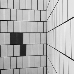 A Wall Covered In White And Black Ceramic Tiles
