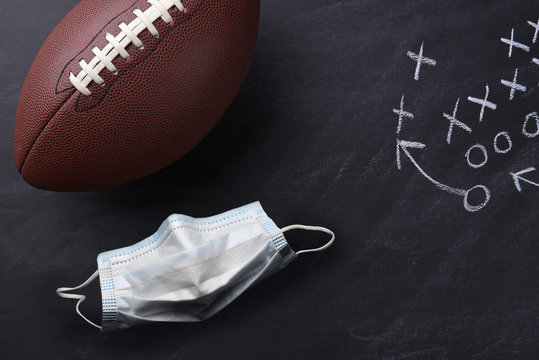 Covid-19 surgical mask and an American style football on a chalkboard with a play diagramed.