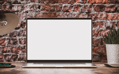 Laptop with blank screen on wooden table in loft interior with vintage brick wall