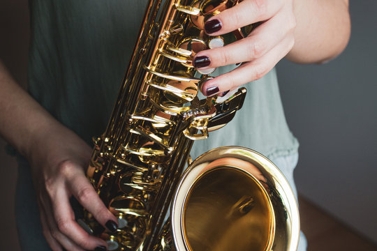 Saxophone girl player hands. Saxophonist playing jazz music. Alto sax musical instrument closeup. Painted nails.