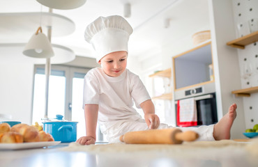Cute little boy in chef's hat playing with the dough and rolling pin in the kitchen