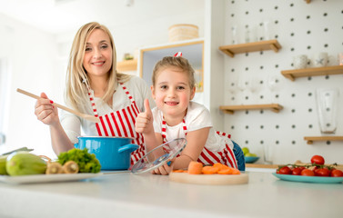 Mother and daughter having fun while cooking together in kitchen at home