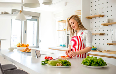 Young smiling woman preparing healthy meal with vegetables in bright modern kitchen