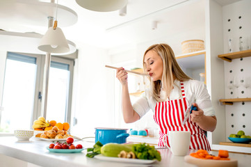 Young woman tasting food with wooden spoon in bright modern kitchen