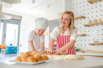Little boy  in chef's hat and his mother preparing the dough, bake rolls