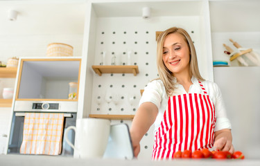 Smiling woman in kitchen reading new recipe on digital tablet while preparing meal